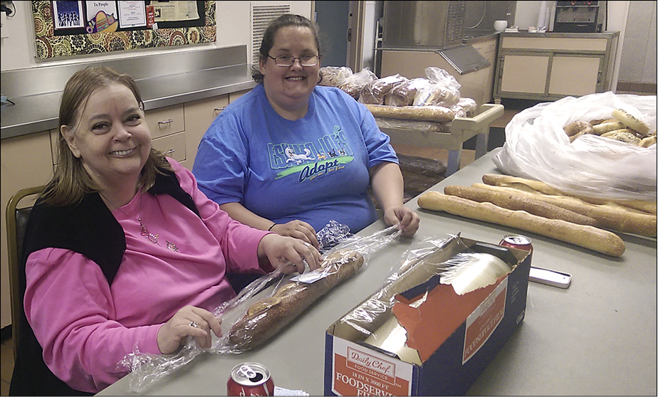 Jonna Lawrence, left, and Courtney Carruth, new members of Tulsa-Boston Avenue, wrap surplus bread donated by a bakery to be given to COMPassion guests.