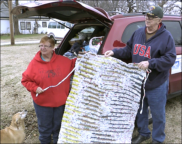 Mary and Lenny Kaplan show off a sleeping mat that was hand-crocheted from plastic grocery bags. The mats, which offer some cushioning and protection from the hard ground, are much-requested by people who live outside.